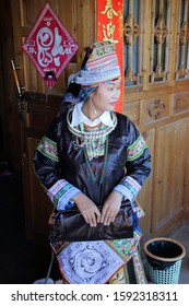 Kaili, China - October 29, 2019: At Hundreds of Birds Miao Village, portrait of a girl, wearing typical clothes and headgear of Miao minority
