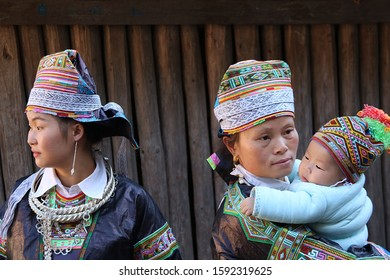 Kaili, China - October 29, 2019: At Hundreds of Birds Miao Village, portrait of a girl, a woman and a baby, wearing typical clothes and headgear of Miao minority