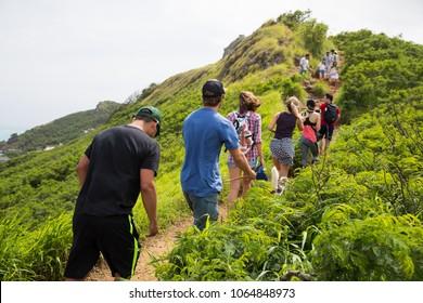KAILUA, HAWAII - FEBRUARY 25, 2018: Tourists take pictures and hike up the ridge at the Lanakai Pillbox Hike over Kailua, Oahu Hawaii.