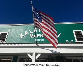 Kailua, Hawaii / USA - 03 26 2019: Hawaiian and United States flag waving in front of Kalapawai Market, near Kailua Beach, Hawaii.