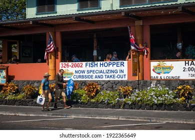 KAILUA-KONA, HI, U.S.A. - JAN. 2, 2021: A couple with masks walks by Fish Hopper, a popular, upscale seafood restaurant with outdoor dining advertising curbside and takeout food in downtown Kona.