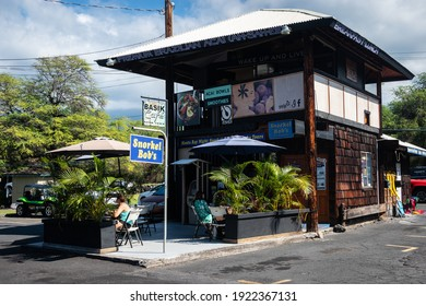 KAILUA-KONA, HI, U.S.A. - JAN. 3, 2021: Diners sit outside at Basik Cafe and Snorkel Bob's shop in downtown Kona.