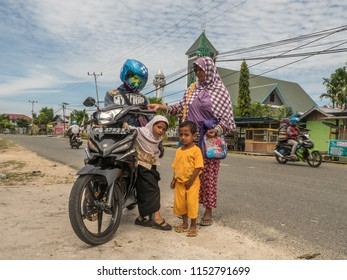Kaimana, Indonesia - January 31, 2018:  Indonesian family with motorbike on the street in the small village on the West Papua