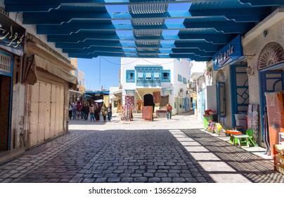 KAIROUAN, TUNISIA - APRIL 9: Tourists and locals in the traditional medina market in Kairouan, Tunisia on April 9, 2018