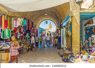 KAIROUAN, TUNISIA - AUGUST 30, 2015: The crowded alleyway of the souk in Medina with garment and shisha (hookah) stalls, on August 30 in Kairouan.