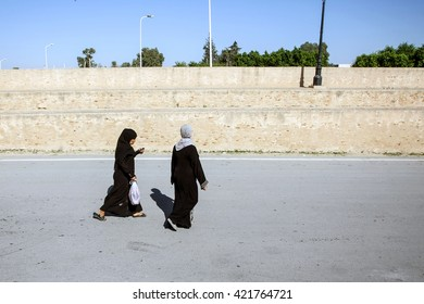 KAIROUAN, TUNISIA - SEPTEMBER 16, 2012 : Two Muslim women passing by the walls surrounding the  Great Mosque of Kairouan in the street of Kairouan, Tunisia.