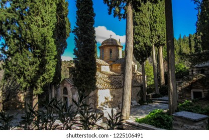 The Kaisariani Monastery beautiful an Eastern Orthodox historical holy place built on the north side of Mount Hymettus in sunny day with clear blue sky, near Athens, Greece