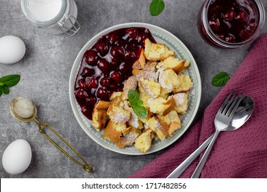 Kaiserschmarren or Kaiserschmarrn is a traditional Austrian or German sweet pancake dessert, with icing sugar and berry, cherry sauce or rote grutze jam. Top view.
