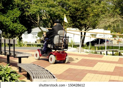 KAITAIA, NZ - AUG 15 2013:Elderly man drive mobility scooter outdoors.Currently the US Medicare will not approve a power wheelchair for persons who do not need to use the chair inside their own home.