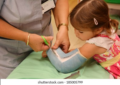KAITAIA, NZ  - MAR 27 2014:Nurse removing an arm orthopedic cast of a child (Talya Ben-Ari age 3). Forearm fractures account for 40% to 50% of all childhood fractures.
