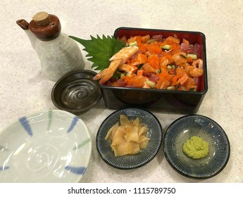 Kaizen shirashi and shoyu bottle, wasabi with pickled ginger on side dish in decorations set of Japanese food on stone table