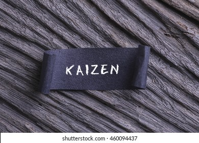 KAIZEN word written on Black papper with wooden background. RUSTIC AND GRANY EFFECT.