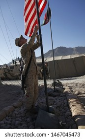 Kajaki, Afghanistan - March 20, 2012: US Marines raise the American flag next to the Afghan flag upon a US military forward operating base.
