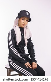Kajang, Malaysia - Oct 17, 2019 : Attractive hijab girl wearing black adidas sports wear sitting on a chair isolated over white background. Lifestyle sport wear concept.