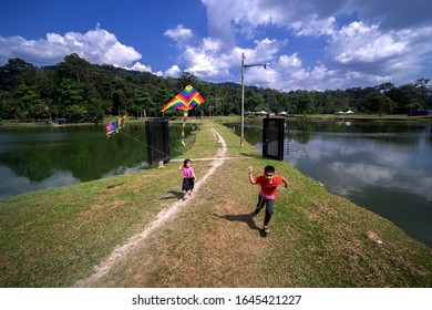 Kajang,Malaysia- January 25th, 2020.  Boys and girls enjoy playing kites near the fishing pond among the concept of recreation introduced by the fishing pond operator.
