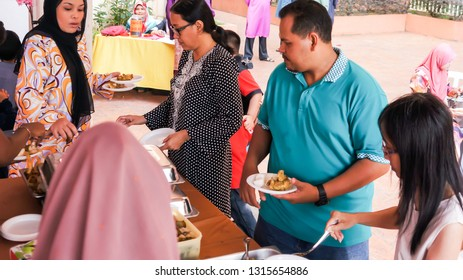 KAJANG,MALAYSIA-JULY 8,2018: A group of residents queing to take a food during their community event near Kajang,Selangor