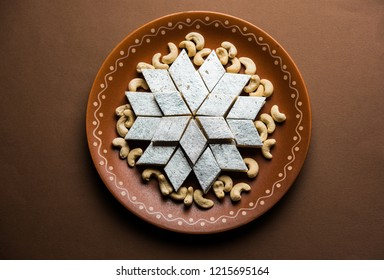 Kaju Katli is a Diamond shape Indian sweet made using cashew sugar and mava, served in a plate over moody background. selective focus