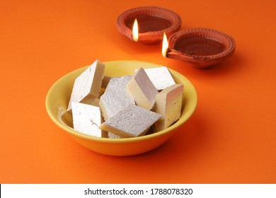 Kaju katli is a traditional Indian festive sweet made from kaju or cashews and khoya. Kaju katli in a yellow bowl with earthen lamp lit in the background.