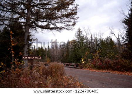 Kakabika Falls sign in the upper peninsula of Michigan on a cold autumn day along the narrow road with the bridge in the backgrouind. Marenisco Township