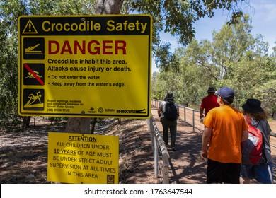 Kakadu national park, Australia - March 12th, 2020: Tourists walking next to a crocodile safety warning sign.