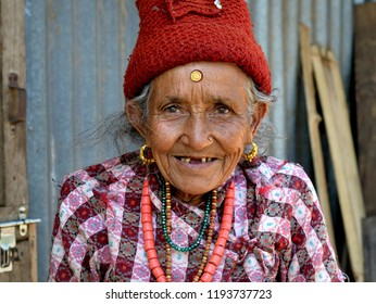 KAKANI, HELAMBU / NEPAL - MAY 11, 2018: Very old Nepali Hyolmo (Yolmo) woman with a massive golden bindi on her forehead poses for the camera, on May 11, 2018.