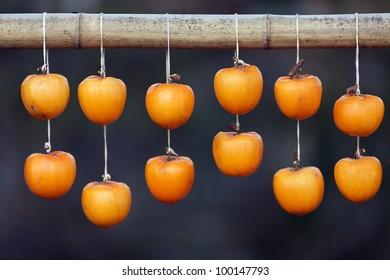 kaki fruit hanging on bamboo stick drying, Japan