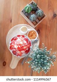 Kakigori or Bingsu strawberry cheesecake on wooden table.