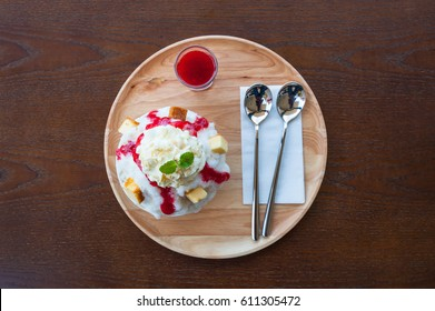 Kakigori strawberry cheesecake. Bingsu strawberry cheesecake from top-view. Bingsoo: white smoothie ice, cream, strawberry, Sweetened condensed milk mixed of Korean dessert in bowl on wood table