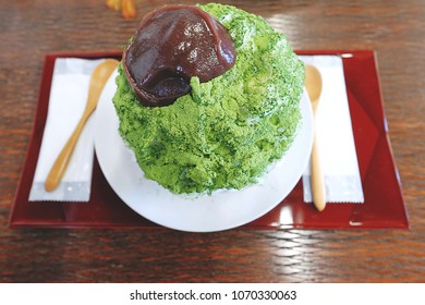 Kakigori,Summer desserts,Popular food, matcha green tea shaved ice topped with matcha powder and red bean paste and served in white dish on a red tray and placed on wooden table.