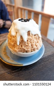 A Kakiori Japanese shaved ice dessert with sweet cream cheese and boba toppings, Thai milk tea Bingsoo or Bingsu with copy space. (soft focus)