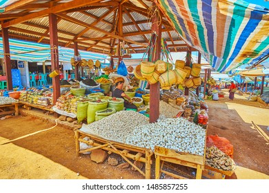 KAKKU, MYANMAR - FEBRUARY 20, 2018: The vendors of local farmers in Kakku market offer garlic, widely spread in region, ginger roots, spices, herbs and dried vegetables, on February 20 in Kakku.
