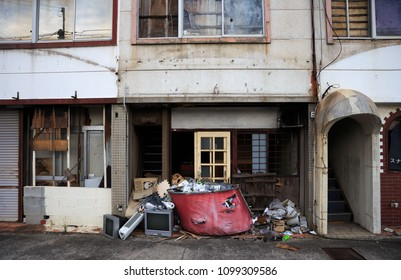 Kakogawa, Japan - May 18, 2018: Pile of electronics and other garbage in front of rundown abandoned buildings