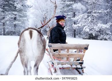 KAKSLAUTTANEN, LAPLAND - January 9th 2016: A Sami man in his reindeer sleigh in Finnish Lapland
