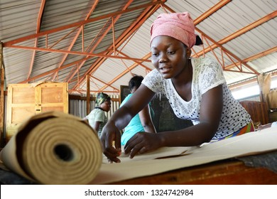 Kakuma, Kenya - May 2018: Portrait of a young woman cutting paper fabric for practising dressmaking in vocational training centre in Kakuma refugee camp.
