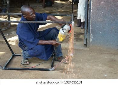 Kakuma, Kenya - May 2018: Young welder grinding metal in vocational training centre in Kakuma refugee camp.