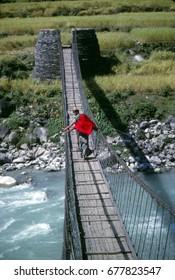 KAL GANDaki, nepal - nov 12, 2002 - Crossing a suspension bridge over the Kali Gandaki river, Himalaya,Nepal