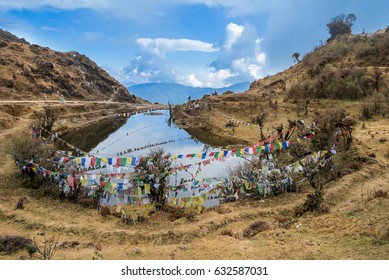 Kala Pokhri, the Black Water Pond with multi-colored prayer flags flung across, on the trekking route to Sandakphu inside the Singalila National Park, Darjeeling, India