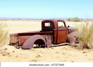 KALAHARI DESERT, NAMIBIA, AFRICA - October 8, 2016. Abandoned  rusty pickup car with Ford logo from the past, stuck in sand in middle of nowhere.