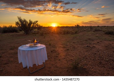 Kalahari Desert, Namibia - March 25, 2019 : Picnic table with white tablecloth, snacks and beverages in the Kalahari desert at sunset.