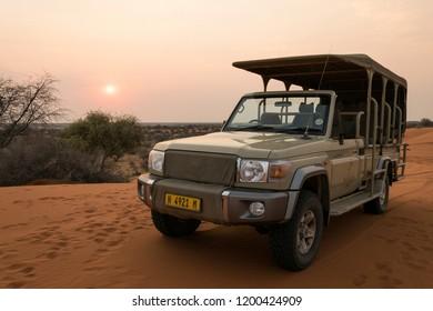 Kalahari desert / Namibia - September 15 2017: Toyota Land Cruiser standing on a dune in Kalahari desert (Namibia) at sunset