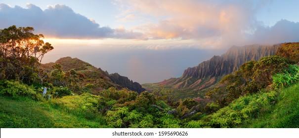 Kalalau lookout panorama on Hawaii island Kauai. Beautiful color sunset with rainy clouds. View of the Kalalau Valley  and Na Pali coast from Koke´e State park.