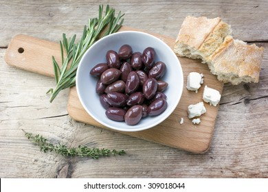 Kalamata black olives in a white bowl, bread, feta cheese and herbs garnish on a rustic wooden table, view from above