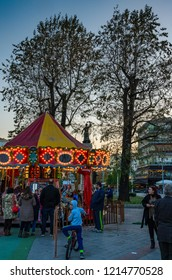 KALAMATA, GREECE - DECEMBER 2015: Christmas atmosphere in Kalamata, Greece with a colorful carousel and people walking at the main square of the city. Messenia, Greece