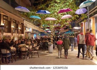 KALAMATA - GREECE DECEMBER 2018: The famous Iatropoulou pedestrian street in Kalamata city decorated for Christmas, with illuminated store fronts, cafes and restaurants. Messenia, Peloponnese, Greece.