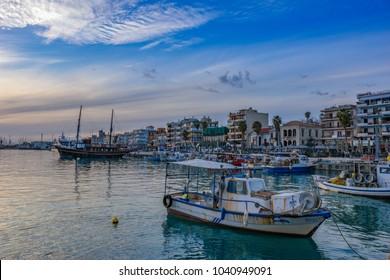 KALAMATA, GREECE - MARCH 2018: Scenic sunset at the port of Kalamata city with many traditional wooden fishing boats along the coast. Kalamata, Messenia, Greece