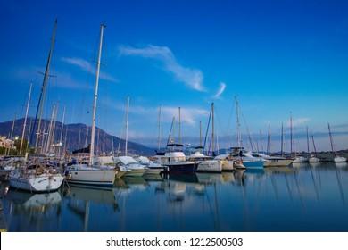 KALAMATA, GREECE - OCTOBER 2016: Scenic view with sailing boats and beautiful reflections in Kalamata's Marina at sunset. Kalamata city, Messenia, Peloponnese, Greece