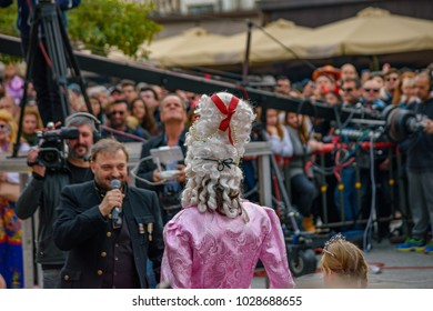Kalamata Messenia, Greece - February 18 2018: People wear deocrated masks and participate in Kalamatas Carnival event. Folk festivals, people parade in groups in Kalamata city, Peloponnese, Greece