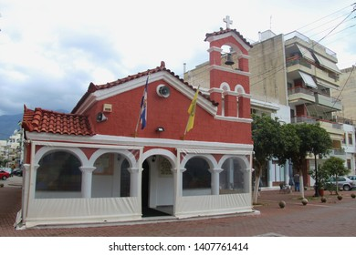 Kalamata, Peloponnese, Greece - April 9, 2019: Small red historic chapel in the middle of the street in Kalamata city. South-east Europe.