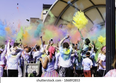 "KALAMAZOO, MICHIGAN - April 12, 2014: Runners in a 5K ""fun"" race celebrate by tossing packets of colored powder. Color Run is an event series in the U.S., Europe, South America, and Australia."