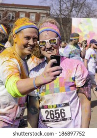 """KALAMAZOO, MICHIGAN, USA - April 12, 2014: Two smiling women runners take a selfie after a 5K """"fun run"""" and dousings of colored powder in an event series called Color Run."""